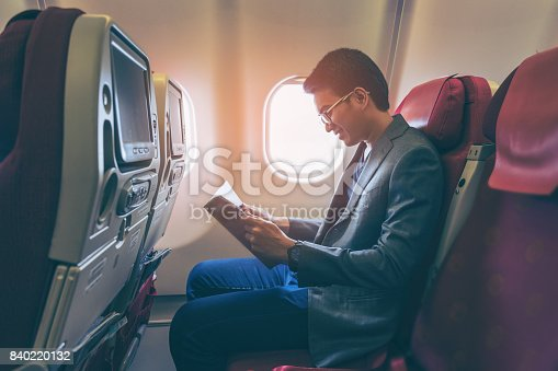 istock Young asian business man smiling and reading a book in airplane 840220132