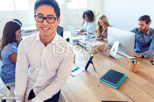 629805626 istock photo Young Asian business manager standing in front of his team. 494089950