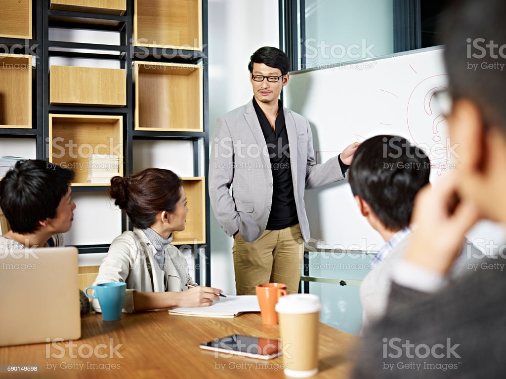 young asian business person facilitating a discussion stock photo