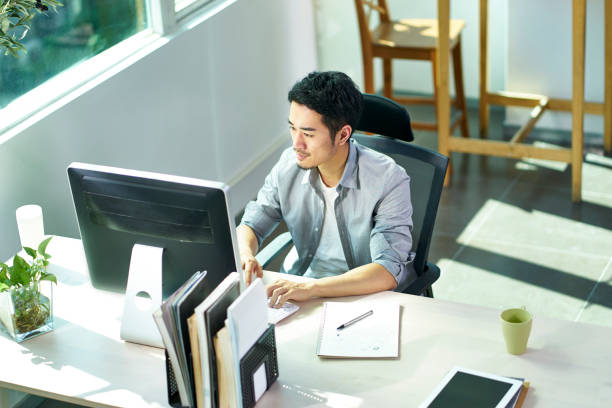young asian business person working in office using computer stock photo