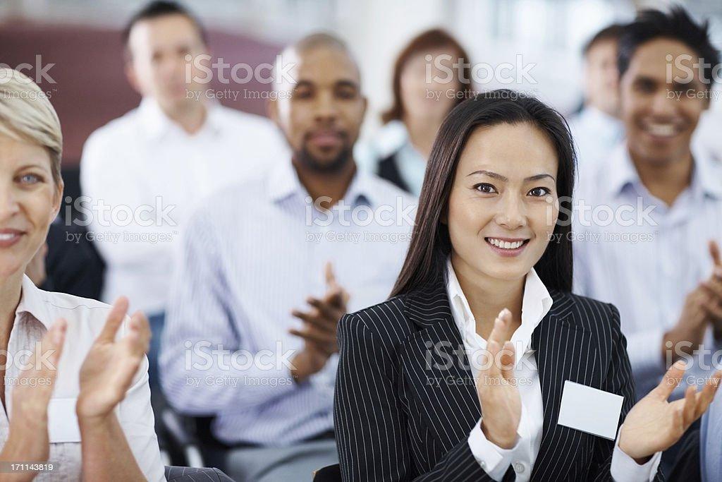 Young Asian business woman at a seminar applauding royalty-free stock photo