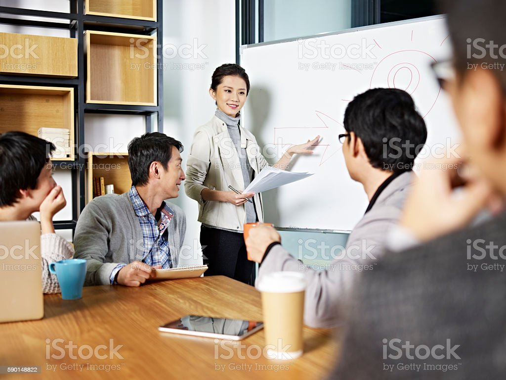 young asian business woman facilitating a discussion stock photo
