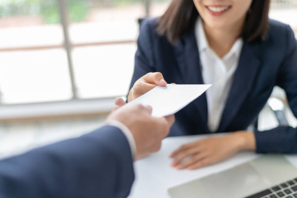 Young Asian business woman receiving salary or bonus money from boss or manager at office happily. Young Asian business woman receiving salary or bonus money from boss or manager at office happily. wages stock pictures, royalty-free photos & images