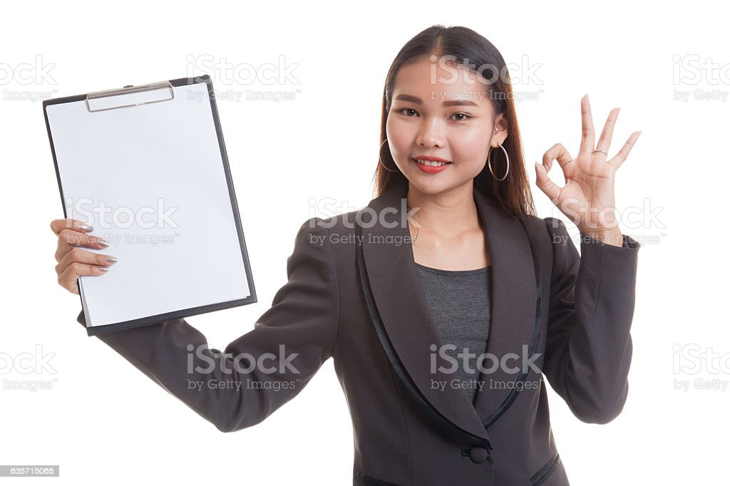 Young Asian business woman show OK and blank clipboard. royalty-free stock photo