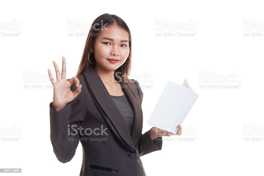 Young Asian business woman show OK with a book. royalty-free stock photo