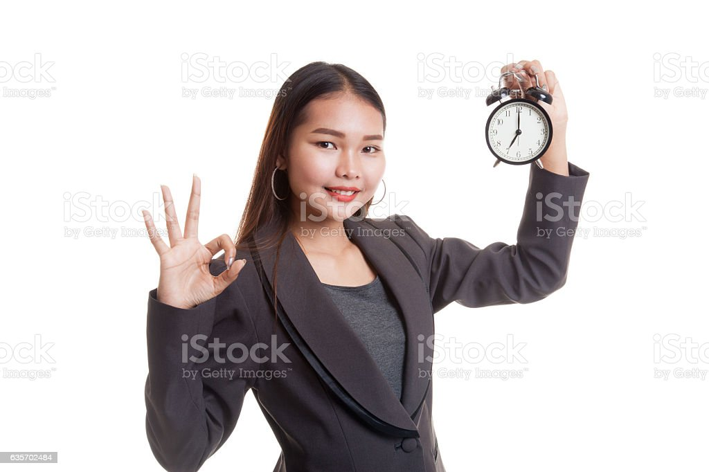Young Asian business woman show OK with a clock. royalty-free stock photo