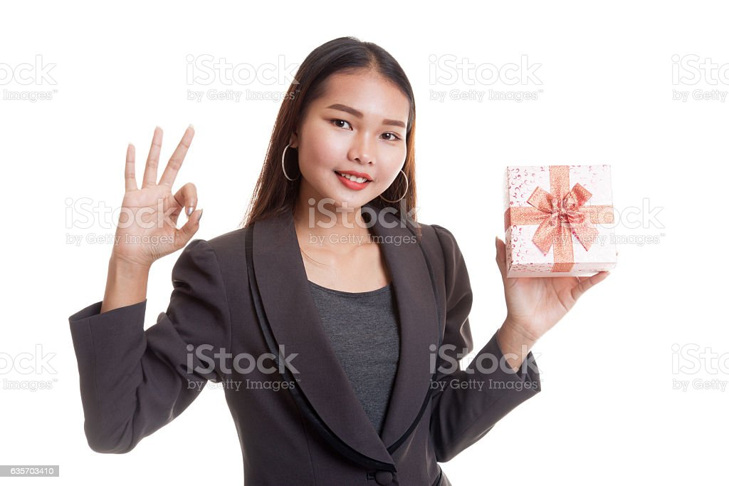Young Asian business woman show OK with a gift box. royalty-free stock photo