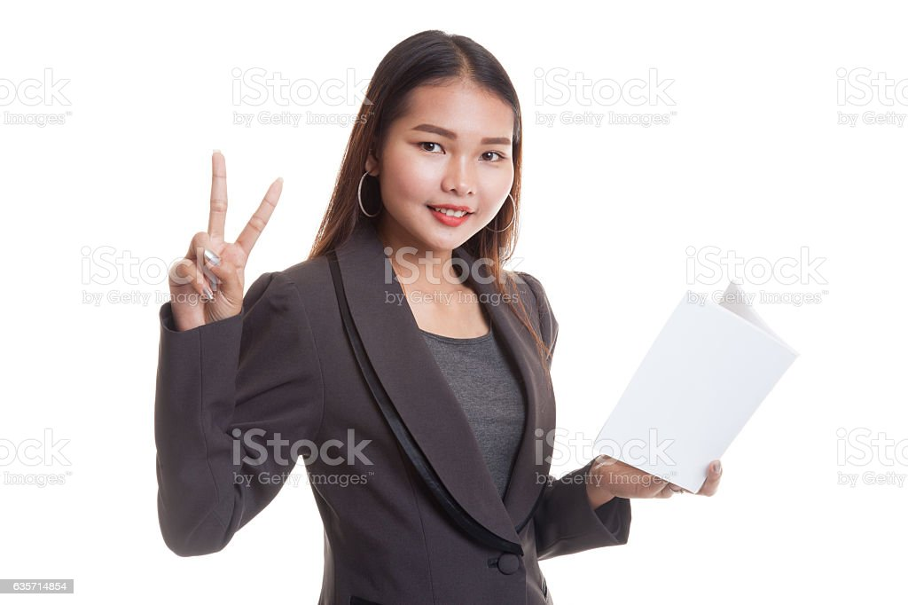 Young Asian business woman show victor sign with a book. royalty-free stock photo