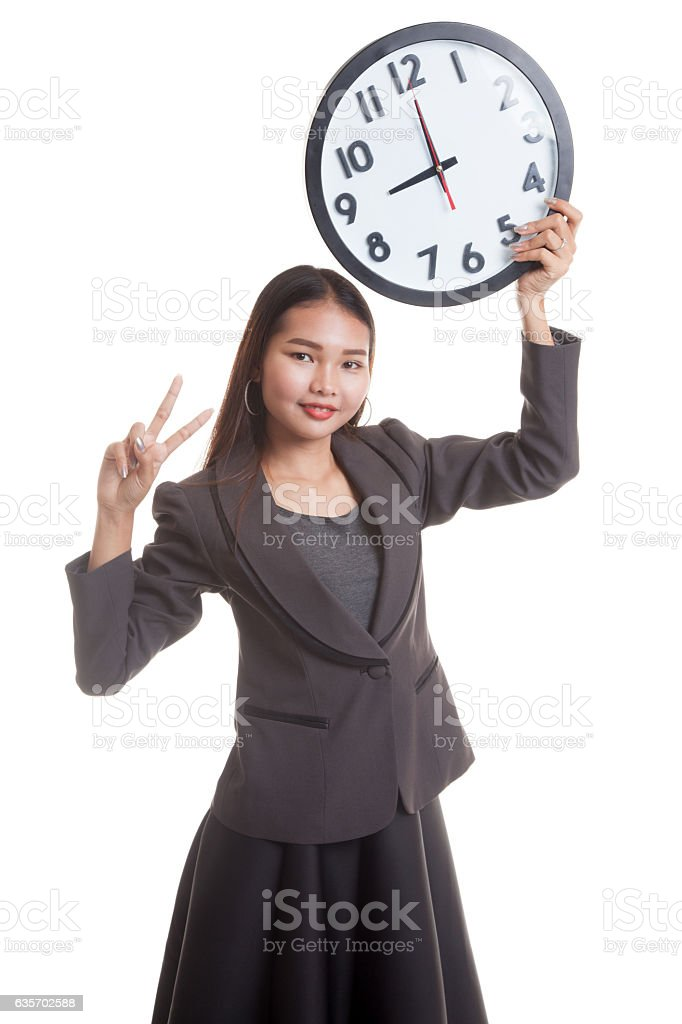 Young Asian business woman show victory sign with a clock. royalty-free stock photo