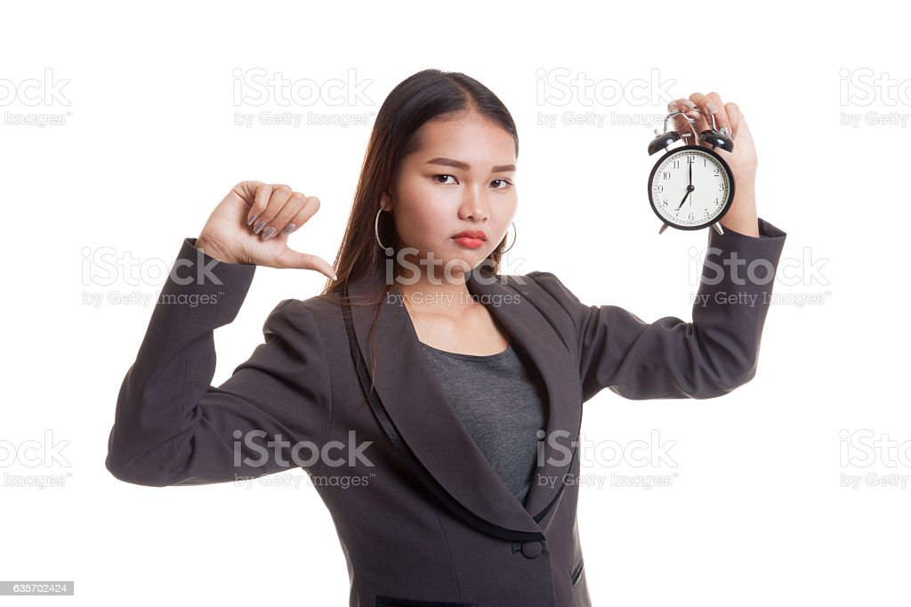 Young Asian business woman thumbs down with a clock. royalty-free stock photo