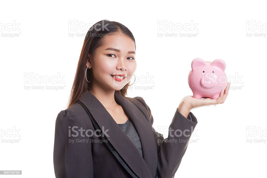 Young Asian business woman with a pig coin bank. royalty-free stock photo
