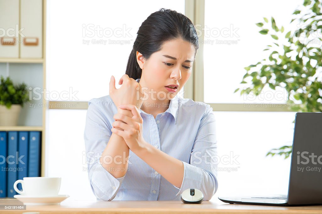 Young asian business woman with pain in wrist stock photo