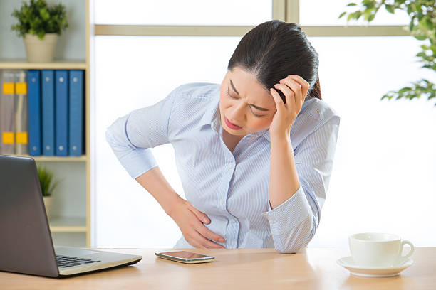 Young asian business woman with stomachache stock photo