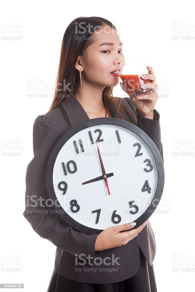 Young Asian business woman with tomato juice and clock. royalty-free stock photo