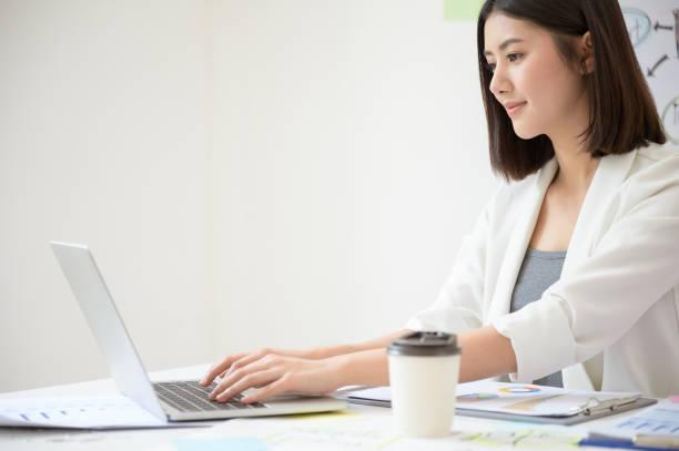 Joven mujer de negocios asiática trabajando en computadora portátil en la sala de oficina con documento de papeleo en el escritorio - foto de stock