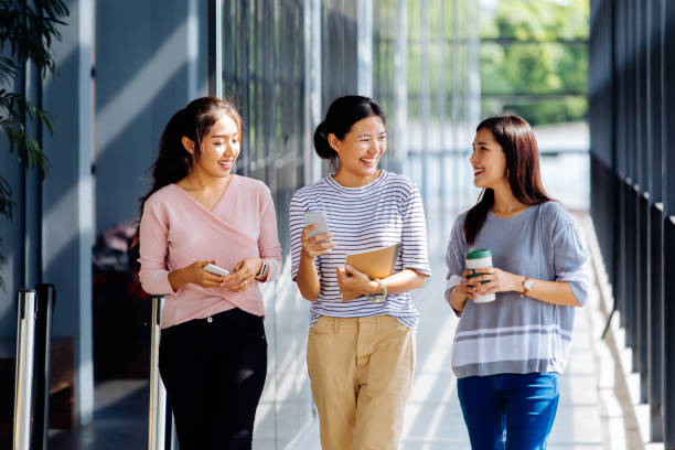 Young Asian business women talking while walking in office building in casual wear stock photo