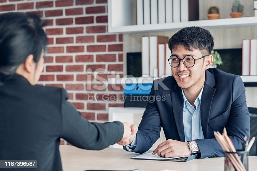 587228412istockphoto young asian businessman and businesswoman handshake about business agreement at meeting table in modern office.business partnership concept.satisfied the deal with client negotiation. 1167396587