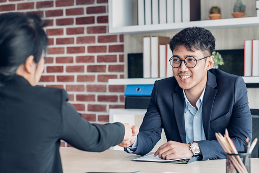587228412 istock photo young asian businessman and businesswoman handshake about business agreement at meeting table in modern office.business partnership concept.satisfied the deal with client negotiation. 1167396587