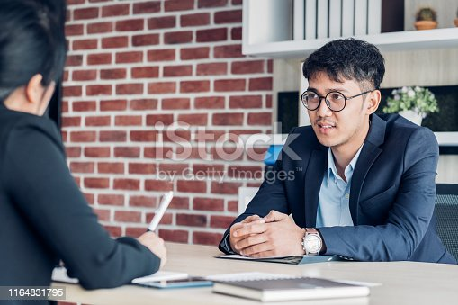 587228412istockphoto young asian businessman and businesswoman talking about business agreement at meeting table in modern office.business partnership concept.satisfied the deal with client negotiation 1164831795