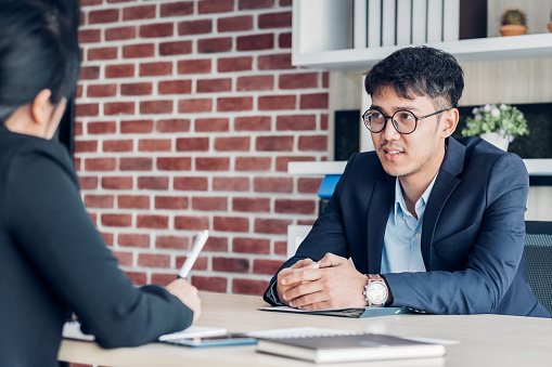 587228412 istock photo young asian businessman and businesswoman talking about business agreement at meeting table in modern office.business partnership concept.satisfied the deal with client negotiation 1164831795