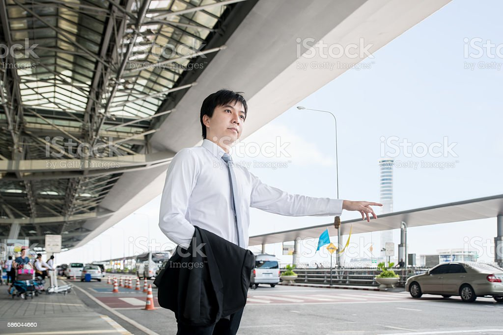 Young Asian businessman calling taxi at the airport. stock photo