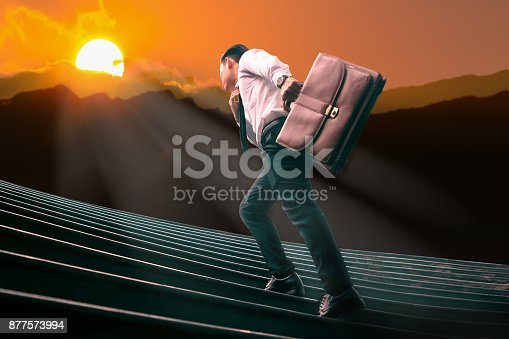 684803840istockphoto Young Asian businessman holding a brown leather bag running on staircase to Silhouette  mountain  and hurdle with the light of the sun of success. 877573994