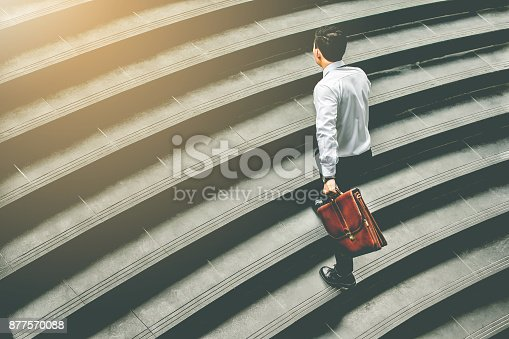 684803840istockphoto Young Asian businessman holding Brown leather bag  working on  staircase go office hurry work time with sunset top view and vintage tone 877570088
