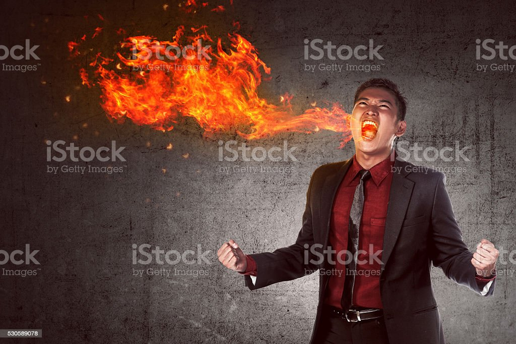 Young asian businessman in anger burning in flame stock photo