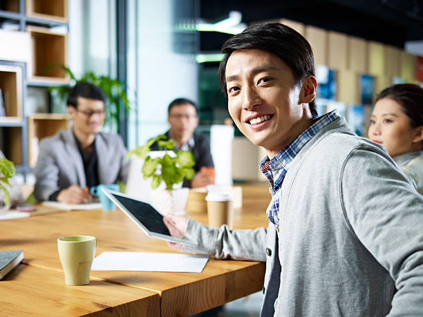 young asian businessman looking at camera young confident asian businessman turning to look at camera during meeting in office. korean ethnicity stock pictures, royalty-free photos & images