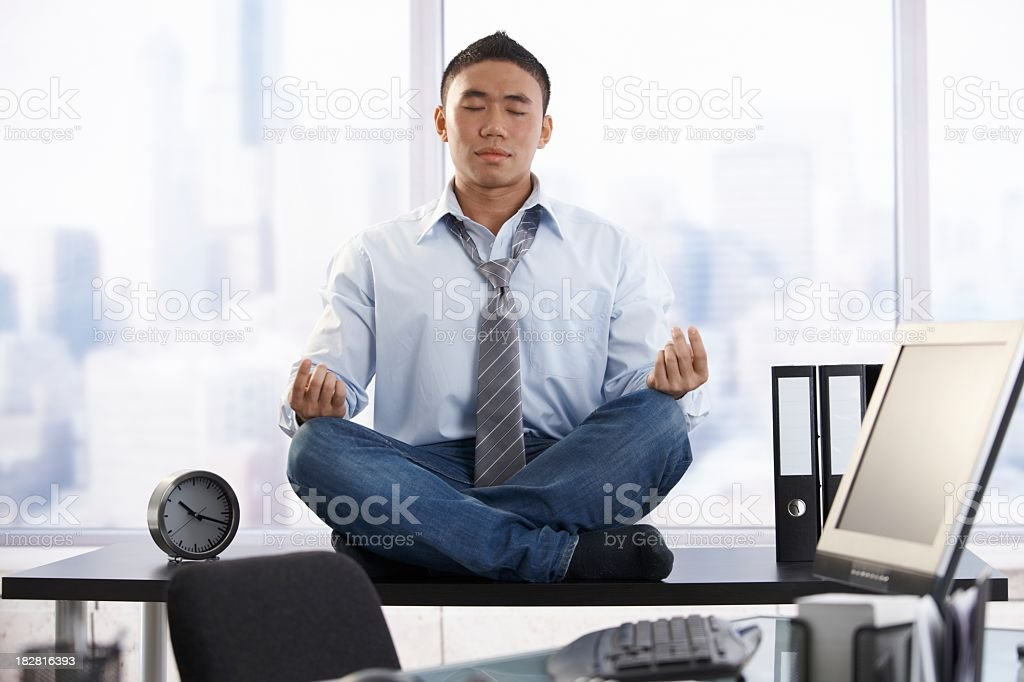 Young asian businessman meditating in office stock photo