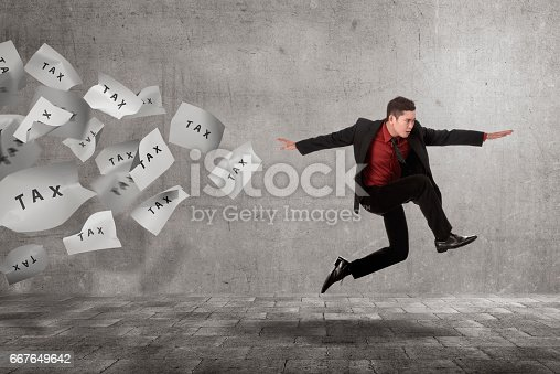 istock Young asian businessman run away from flying paper with Tax text 667649642
