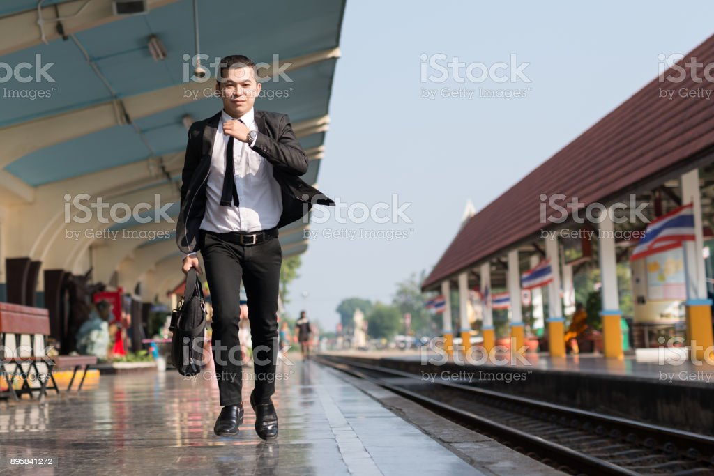 Young Asian Businessman Running To At Train Station In Hand
