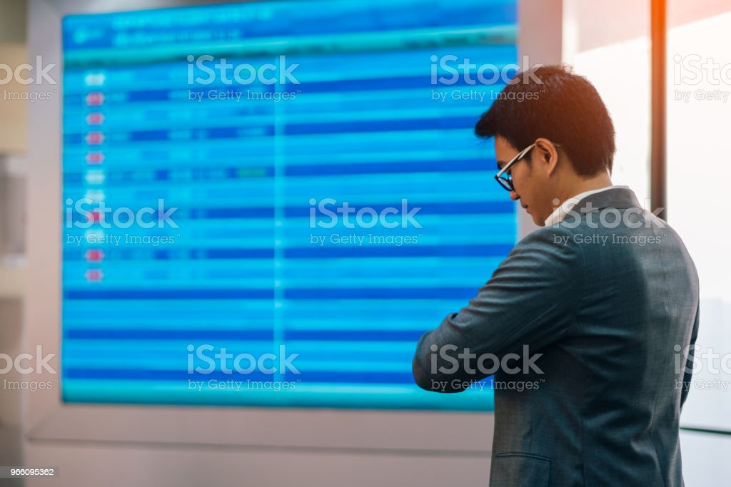Young asian businessman standing near airline schedule and looking at his watch - Стоковые фото Аэропорт роялти-фри