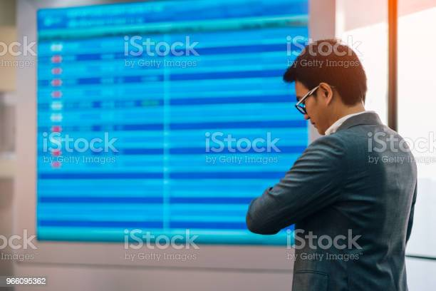 Young Asian Businessman Standing Near Airline Schedule And Looking At His Watch — стоковые фотографии и другие картинки Аэропорт