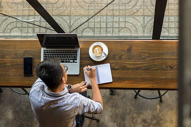 hombre de negocios joven asiática tomar nota junto a computadora portátil sobre una mesa de madera - trabajo freelance fotografías e imágenes de stock