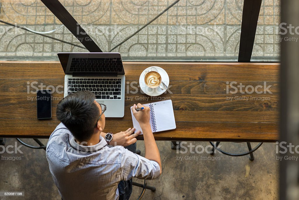 Young Asian businessman taking note beside laptop on wooden table stock photo