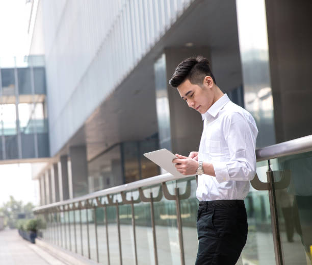 young asian businessman using tablet at office exterior stock photo