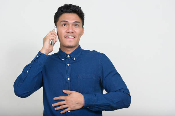 Young Asian businessman wearing blue button down shirt against white background stock photo