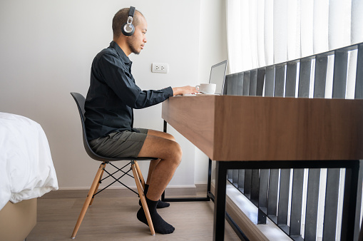 Young Asian businessman wearing shirt and casual shorts while online conference from home.