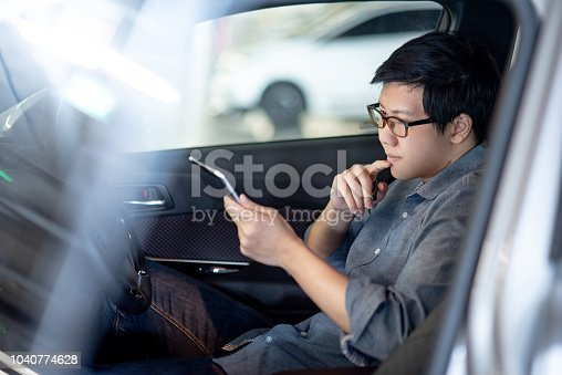 istock Young Asian businessman with glasses reading news on digital tablet while sitting on driver seat in his car. Business and technology concept 1040774628