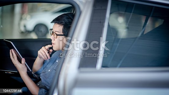 istock Young Asian businessman with glasses reading news on digital tablet while sitting on driver seat in his car. Business and technology concept 1044229144