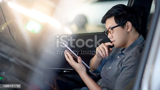 istock Young Asian businessman with glasses reading news on digital tablet while sitting on driver seat in his car. Business and technology concept 1069151732