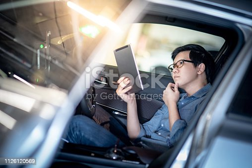 istock Young Asian businessman with glasses reading news on digital tablet while sitting on driver seat in his car. Business and technology concept 1126120569