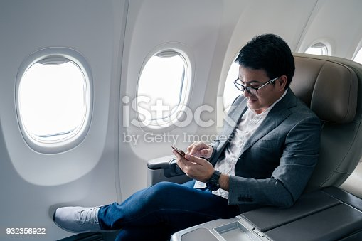 istock Young asian businessman with suit sitting in business first class seat via using smartphone with happiness 932356922