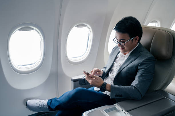 Young asian businessman with suit sitting in business first class seat via using smartphone with happiness