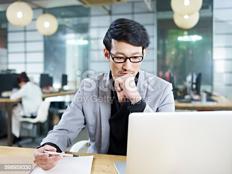 istock young asian businessman working in office 598959330