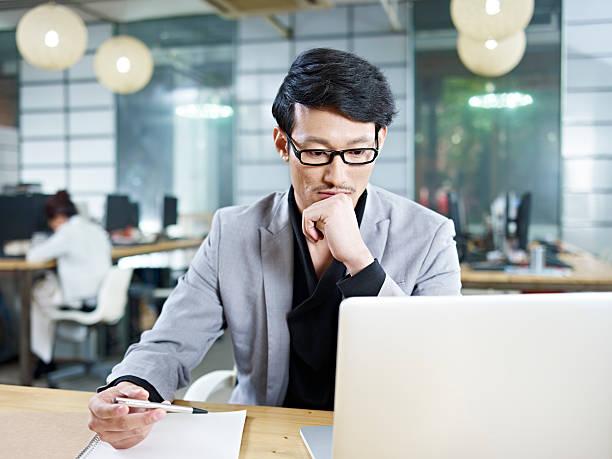 若いアジアのビジネスマンオフィスで働く ストックフォト