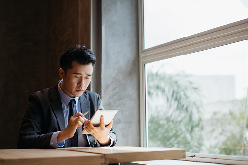 Young asian businessman working with digital tablet and stylus pen