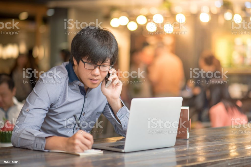 Young Asian Businessman working with laptop in cafe stock photo