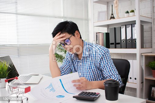 932342408istockphoto Young Asian businessmen are stressed from working at the office. Using a hand touch his head on the desk white. 1201088366